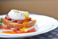 Yema de huevo anaranjada, corriente del huevo escalfado en la salchicha, pan, chesse del queso Feta, ascendente cercano del tomat Imagen de archivo