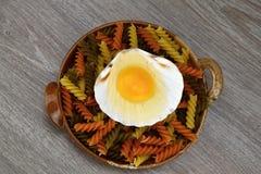 Yema de huevo y albumen Egg en cáscaras del mar en un cuenco de pastas en el fondo de madera imagen de archivo