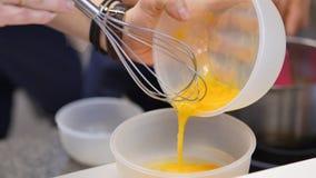 Yemas de huevo azotadas con el azúcar en un bol de vidrio Las yemas de huevo batidas en un cuenco con baten Yema de huevo batida Foto de archivo libre de regalías