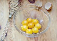 Yemas de huevo del pollo en un bol de vidrio en un fondo de madera Fotografía de archivo libre de regalías