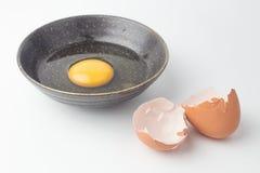 Yemas de huevo una en cuenco negro y cáscaras de huevo quebradas Fotografía de archivo