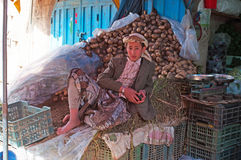 A yemeni boy seated on potatoes outside his shop in the salt market of the Old City of  Sana'a, suq, Yemen, seller, daily life Stock Images