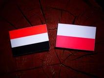 Yemeni flag with Polish flag on a tree stump isolated. Yemeni flag with Polish flag on a tree stump stock illustration