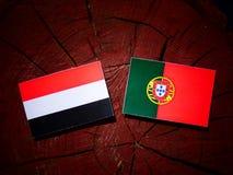 Yemeni flag with Portuguese flag on a tree stump isolated. Yemeni flag with Portuguese flag on a tree stump vector illustration