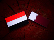 Yemeni flag with Qatari flag on a tree stump isolated. Yemeni flag with Qatari flag on a tree stump Royalty Free Stock Image