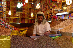 A yemeni man, seated in his shop in the salt market of the Old City of  Sana'a, suq, Yemen, seller, cereals, nuts, daily life Stock Photos