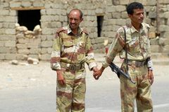Yemeni military men hold hands at the security checkpoint, Hadramaut valley, Yemen. Royalty Free Stock Image