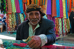 A yemeni old man pays after shopped at the fabric store in the salt market of the Old City of  Sana'a, Yemen, turban, scarves, fou Stock Photography