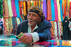 A yemeni old man pays after shopped at the fabric store in the salt market of the Old City of Sana'a, Yemen, turban, scarves. The Old City of Sana'a, the oldest royalty free stock photos