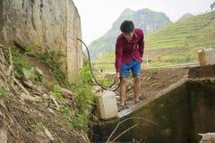 Yen Bai Vietnam - April 11, 2014: Den oidentifierade mannen häller vatten från den byggda behållaren av vatten som samlas från vå Fotografering för Bildbyråer