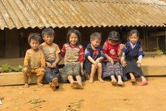 Yen Bai Vietnam - April 12, 2014: Oidentifierade Hmong barn som framme spelar på lekplats av där hus under solljus Hmen arkivbilder