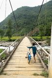 Yen Bai, Vietnam - Sep 18, 2016: Vietnamese Hmong ethnic minority boy walking on old wooden bridge with his bicycle Stock Photography