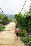 Yen Bai, Vietnam - Sep 18, 2016: Vietnamese Hmong ethnic minority girl walking home on old small chain wooden bridge from school w Stock Images