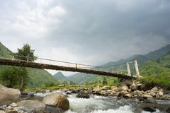 Yen Bai, Vietnam - Sep 18, 2016: A week and small bridge crossing river in area of ethnic minorities in Mu Cang Chai district, wit. H people walking on the Stock Photography