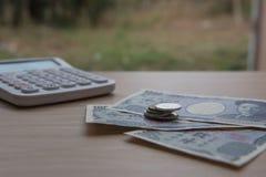 Yen della moneta del primo piano e banconote giapponesi e calcolatore su fondo di legno valuta del Giappone Fotografia Stock Libera da Diritti
