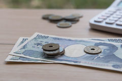 Yen della moneta del primo piano e banconote giapponesi e calcolatore su fondo di legno valuta del Giappone Immagine Stock Libera da Diritti