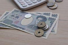 Yen della moneta del primo piano e banconote giapponesi e calcolatore su fondo di legno valuta del Giappone Immagine Stock