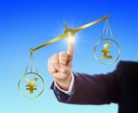 Yen Sign Outweighing The Pound auf einer goldenen Skala Stockbilder