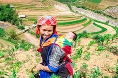 YENBAI, VIETNAM - MAJ 16, 2014 - etnisk mamma och hennes barn som går att arbeta Royaltyfri Bild