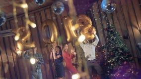 Yendo de fiesta los amigos sostienen los globos con el número 2018 en secuencias almacen de metraje de vídeo