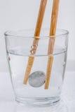 Yenes japoneses de la moneda que se sostienen por los palillos de madera en un vidrio de w Imagenes de archivo