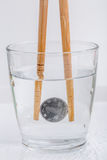 Yenes japoneses de la moneda que se sostienen por los palillos de madera en un vidrio de w Fotos de archivo libres de regalías