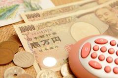 Yenes japoneses (dinero de los diez milésimos) con la calculadora Fotografía de archivo