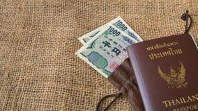 Yenpengar- och yenmynt med passet på säckbakgrund Fotografering för Bildbyråer