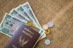 Yenpengar- och yenmynt med passet på säckbakgrund Royaltyfri Bild