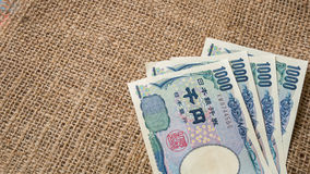 Yenpengar- och yenmynt med passet på säckbakgrund för trav Royaltyfria Bilder