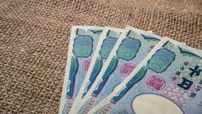 Yenpengar- och yenmynt med passet på säckbakgrund för trav Arkivbilder