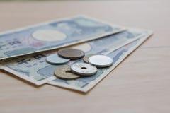 Yens et billets de banque de pièce de monnaie de plan rapproché japonais sur le fond en bois actualité du Japon Images stock