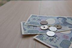 Yens et billets de banque de pièce de monnaie de plan rapproché japonais sur le fond en bois actualité du Japon Photo stock