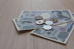 Yens et billets de banque de pièce de monnaie de plan rapproché japonais sur le fond en bois actualité du Japon Image stock