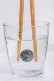 Yens japonais de pièce de monnaie se tenant par les baguettes en bois dans un verre de W Photos libres de droits