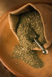 Yerba mate. Bag, opened on wood plate stock image