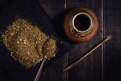 Yerba mate and calabash with bambilla on a black wooden background royalty free stock photography