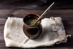 Yerba mate in ceramic matero with bombilla on linen bag on wooden table. Royalty Free Stock Photo