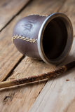 Yerba mate gourd and a bombilla straw on aged wood background, close up Stock Image