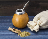 Yerba mate in gourd matero on blue woooden table Stock Image
