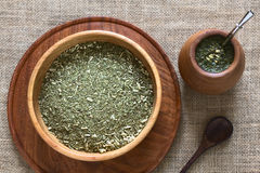 Yerba Mate Tea. South American yerba mate (mate tea) dried leaves in wooden bowl with a wooden mate cup and bombilla (straw) filled with tea next to it royalty free stock image