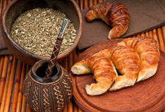 Yerba Mate tradition. Calabash cup for mate and croissants, with yerba mate in the foreground. Mate is a very popular tradition in Argentina and Uruguay stock images