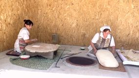 Yerevan, Armenia - 20170614 - Two women make lavash in traditional manner stock footage