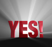 Yes!. Red word YES! on dark background and brilliantly backlit with light rays shining through Royalty Free Stock Photos