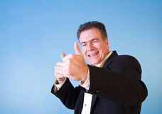 YES!!. A man giving and elated thumbs up taken against a blue background Stock Photo