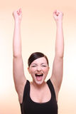 Yes!. Woman celebrating with arms raised, in front of a peach background royalty free stock photography