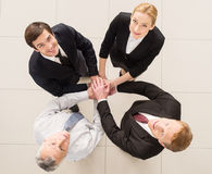 Yes, we are the best!. Top view of four cheerful people in formalwear clasping their hands together and looking at camera Royalty Free Stock Photography