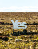 Yes in big white wooden letters with Scottish moorland in the background Royalty Free Stock Photo