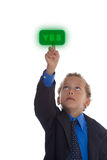 YES button. Boy dressed as businessman pushes the green YES button royalty free stock images