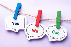 Yes we can. Paper bubbles with clip hanging on the line against purple background Royalty Free Stock Photos
